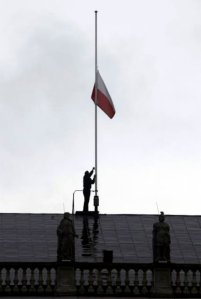A man lowers the Polish national flag at the top of the Presidential Palace to half mast in Warsaw April 10, 2010. Polish President Lech Kaczynski was killed when a plane carrying 132 people crashed in thick fog on its approach to a Russian airport on Saturday, killing everyone on board, officials said. REUTERS/Kacper Pempel (POLAND - Tags: POLITICS DISASTER)